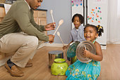 Father and children playing with pots and pans in kitchen