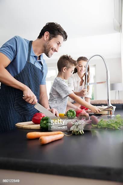 Father and children preparing food in kitchen