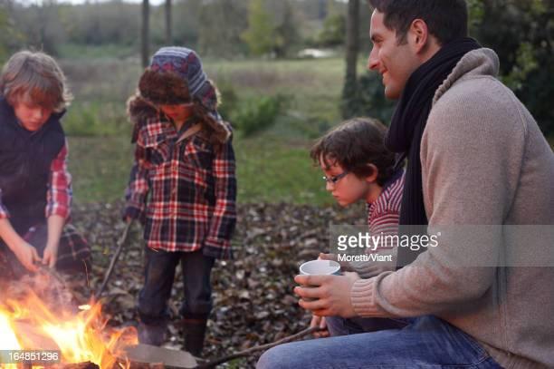 Father and children sitting around bonfire