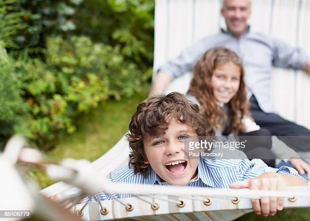Father and children sitting in hammock