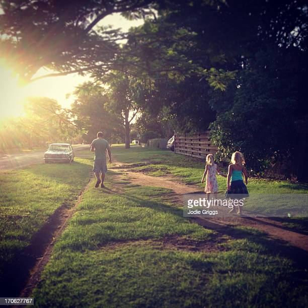 Father and children walking along path