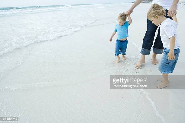 Father and children walking in surf