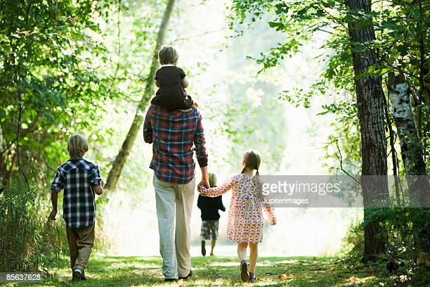 Father and children walking in woods