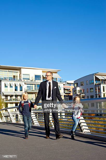 Father and children walking on footbridge