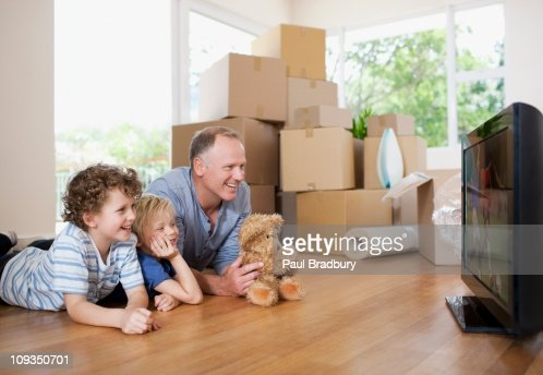 Father and children watching television in new house : Stock Photo