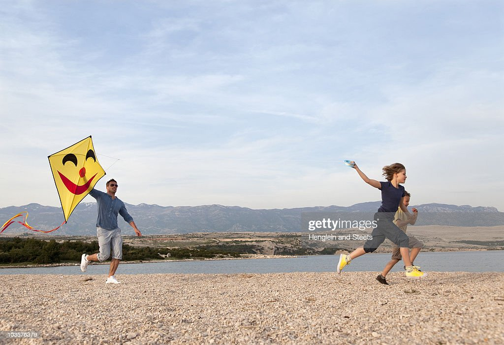 Father and children with kite at beach : Stock Photo