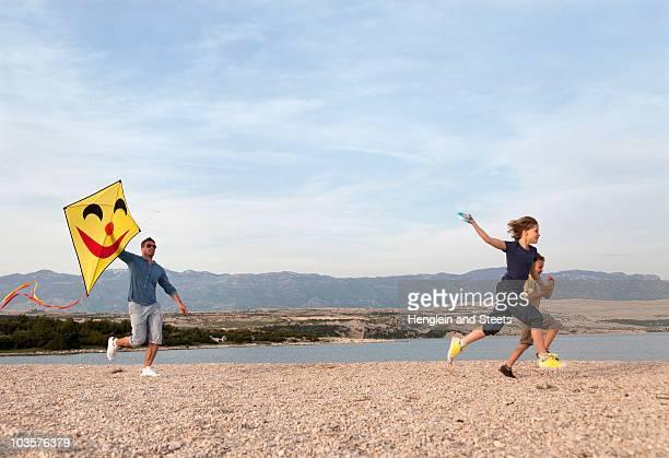 Pai e filhos com Pipa na praia