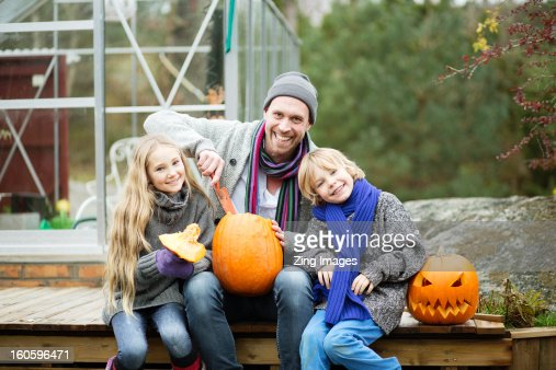 Father and children with pumpkins : Stock Photo
