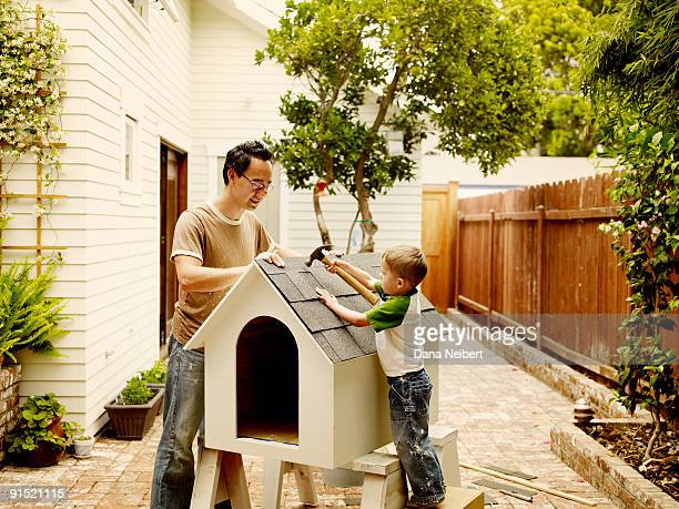 Father and children work on dog house.