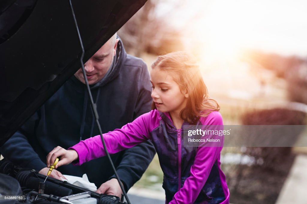 father and daugher checking oil in car : Stock Photo