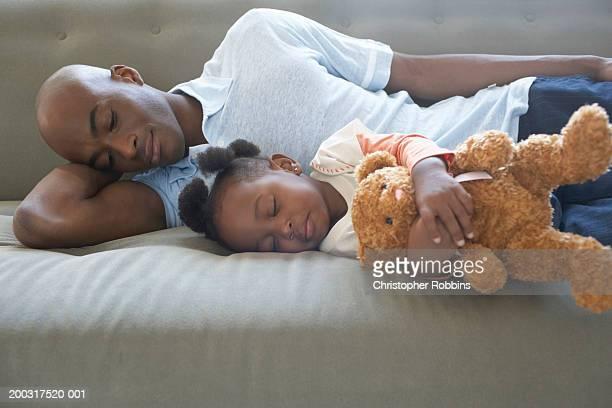 Father and daughter (2-4) asleep on sofa