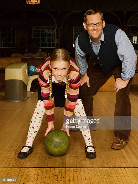 Father and daughter at bowling alley