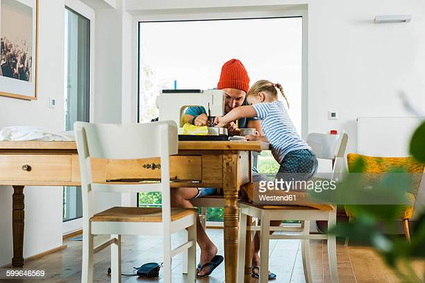 Father and daughter at home using sewing machine