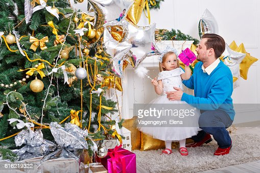 Father and daughter at the Christmas tree. : Stock Photo