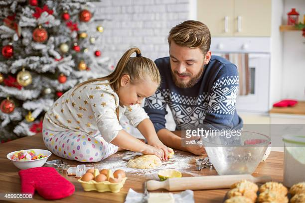 Father and daughter baking in kitchen for christmas.