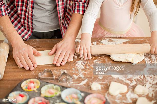 Father and daughter baking in kitchen.