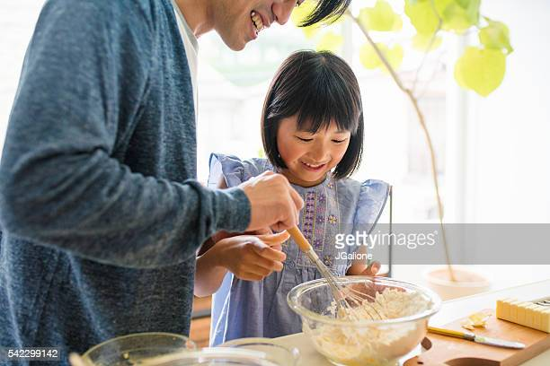 Father and daughter baking together