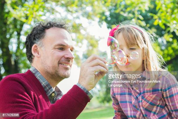 Father and daughter blowing bubbles in garden