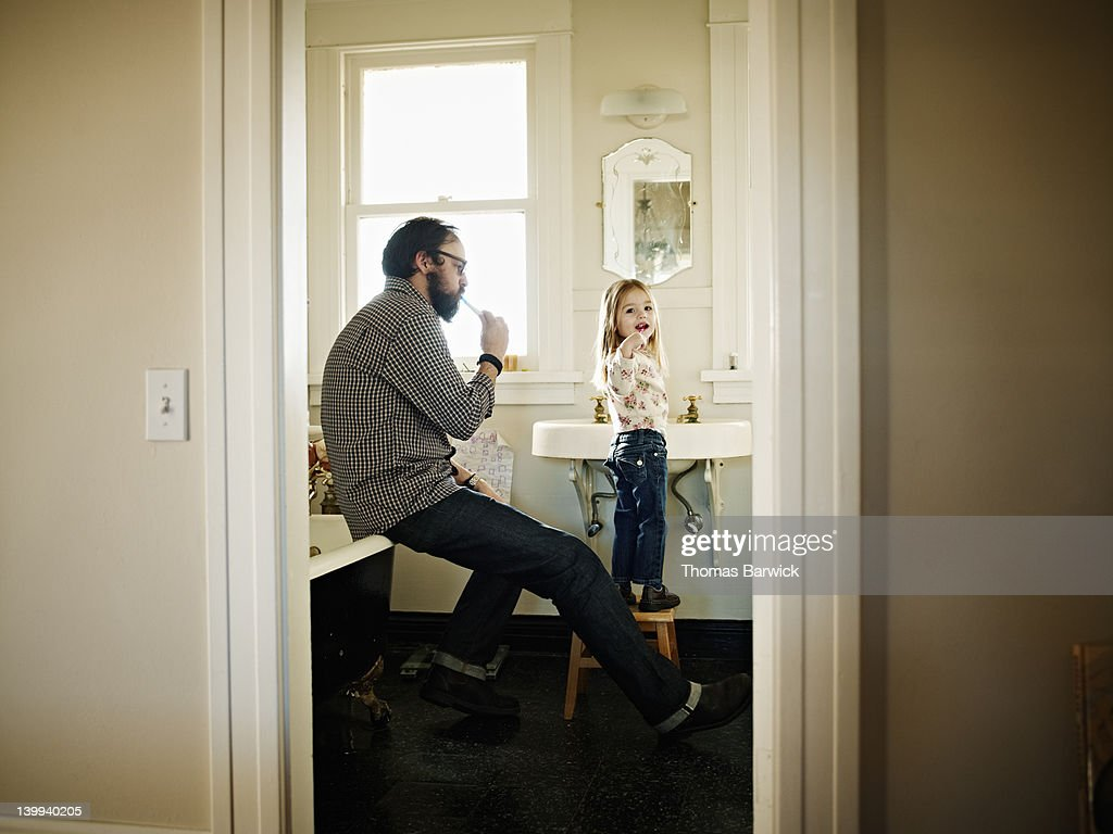Father and daughter brushing teeth in bathroom : Stock Photo