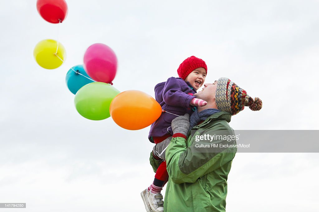 Father and daughter carrying balloons : Stock Photo
