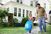 Father and daughter (8-9 years) carrying garbage bag in front of house