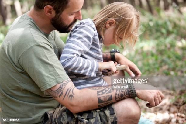 Father and daughter carving in the forest
