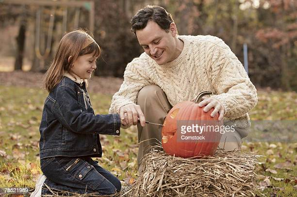 Father and daughter carving pumpkin