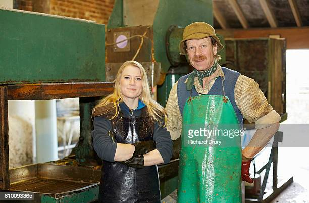Father and daughter cider makers with apple press