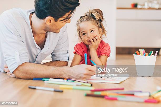 Father and daughter coloring on the floor