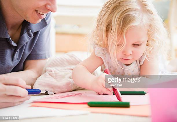 Father and daughter coloring together