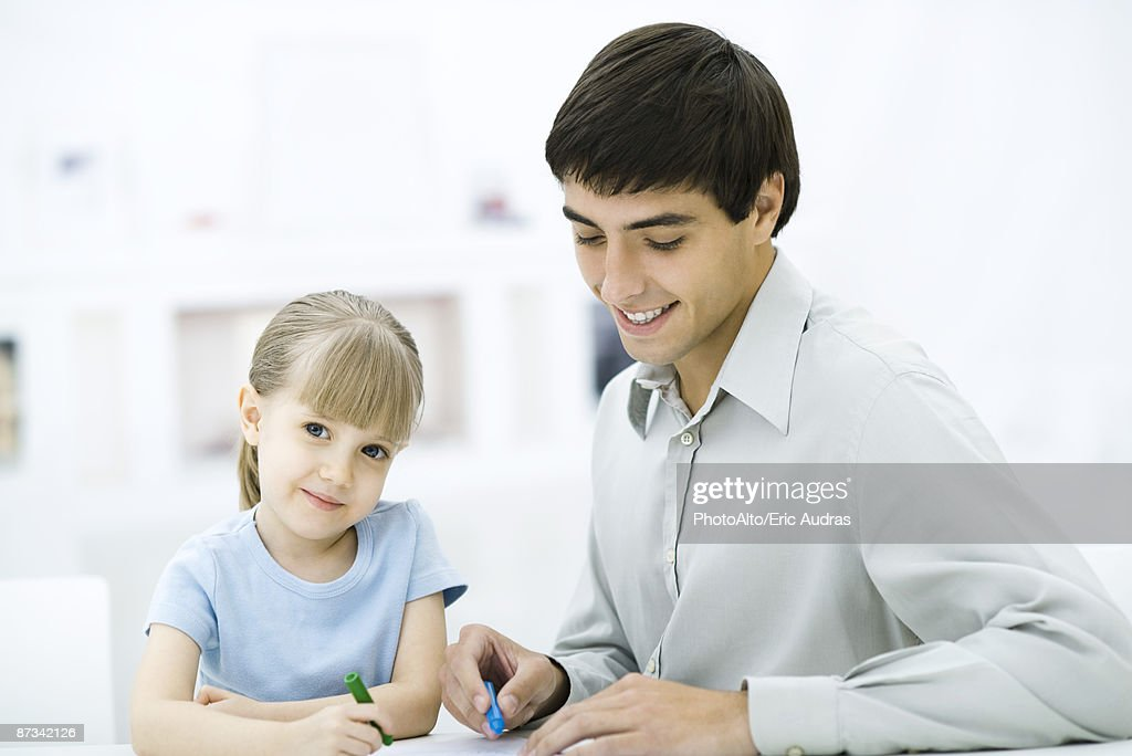 Father and daughter coloring with crayons, girl smiling at camera : Stock Photo