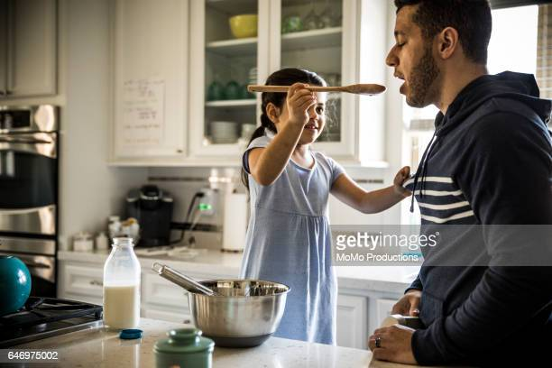 Father and daughter (7yrs) cooking in kitchen