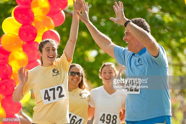 Father and daughter crossing finish line at race