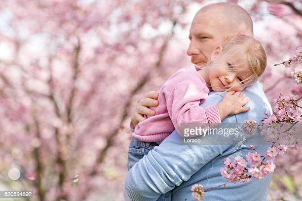 Vater und Tochter Kuscheln unter Kirsche Blumen blühen Bäumen
