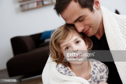 Father and daughter cuddling under coat