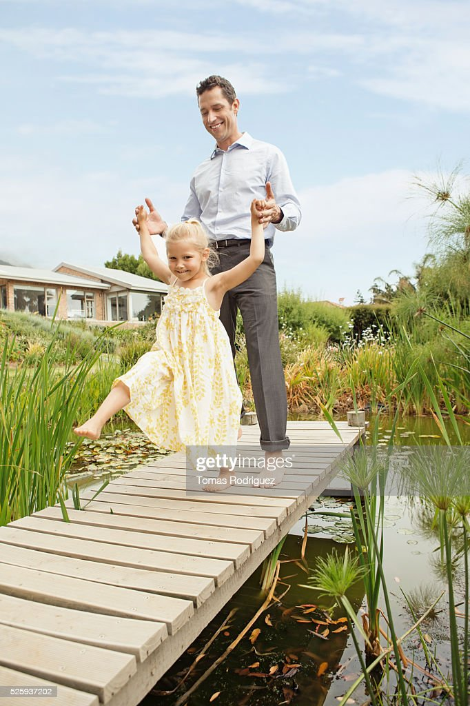 Father and daughter (4-5) dancing on jetty : Bildbanksbilder