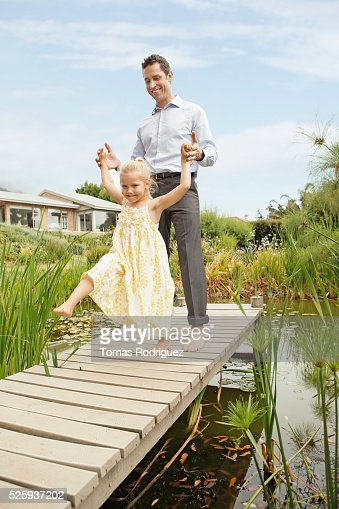 Father and daughter (4-5) dancing on jetty : Stock-Foto