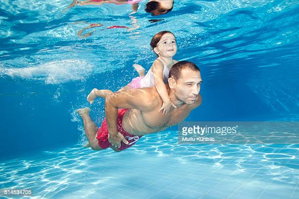 Father and daughter diving in the pool