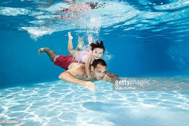 Vater und Tochter beim Tauchen im pool