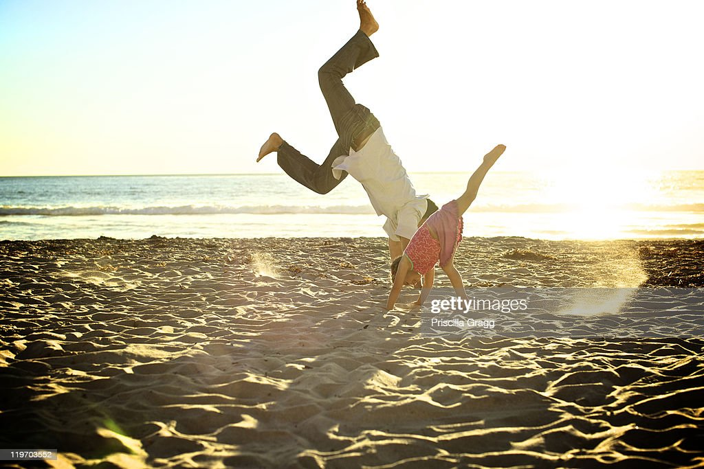 Father and daughter doing cartwheels on beach