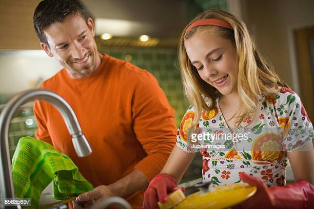Father and daughter doing dishes