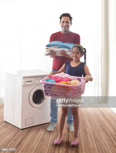 Father and daughter doing laundry in utility room