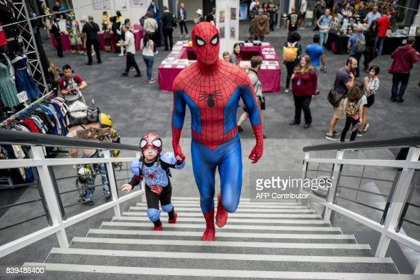 TOPSHOT A father and daughter dressed as Spiderman attend London Super Comic Convention at Business Design Centre in Islington London on August 26...