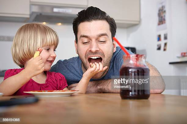 Father and daughter eating breakfast in kitchen