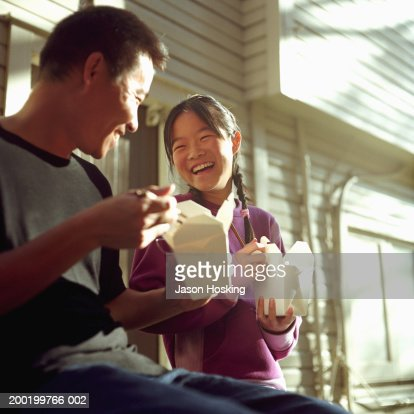 Father and daughter (12-14) eating Chinese food, laughing : Stock Photo