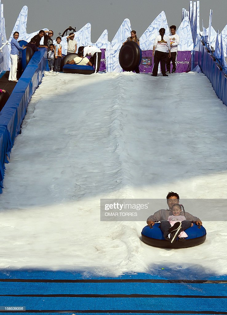 A father and daughter enjoy a sled ride down a slope made of artificial snow in downtown Mexico City on December 18, 2012. The Mexican capital ´s city hall set up different playgrounds with artifical snow and an ice skating rink free of charge for people visiting the downtown area.
