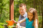 Father and daughter enjoy gardening in backyard. Homegrown organic vegetables.