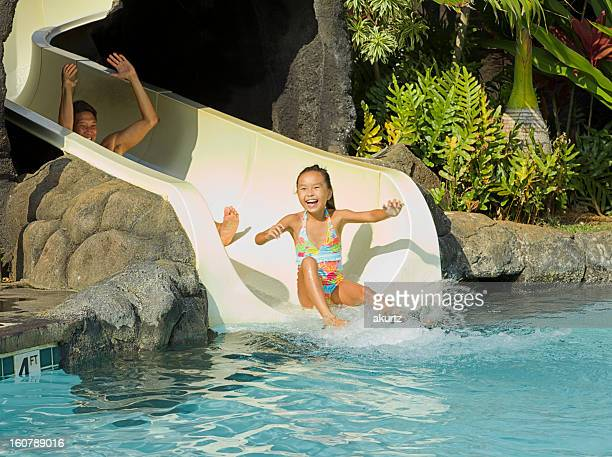 Father and Daughter enjoy sliding down the waterslide