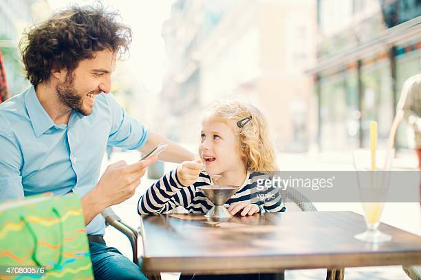 Father and daughter enjoy sunny day in a city.