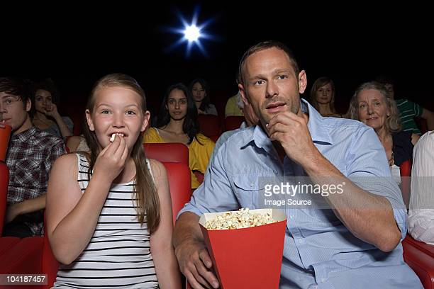 Father and daughter enjoying a movie